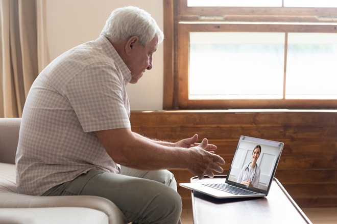 senior patient doing a virtual visit at home on laptop